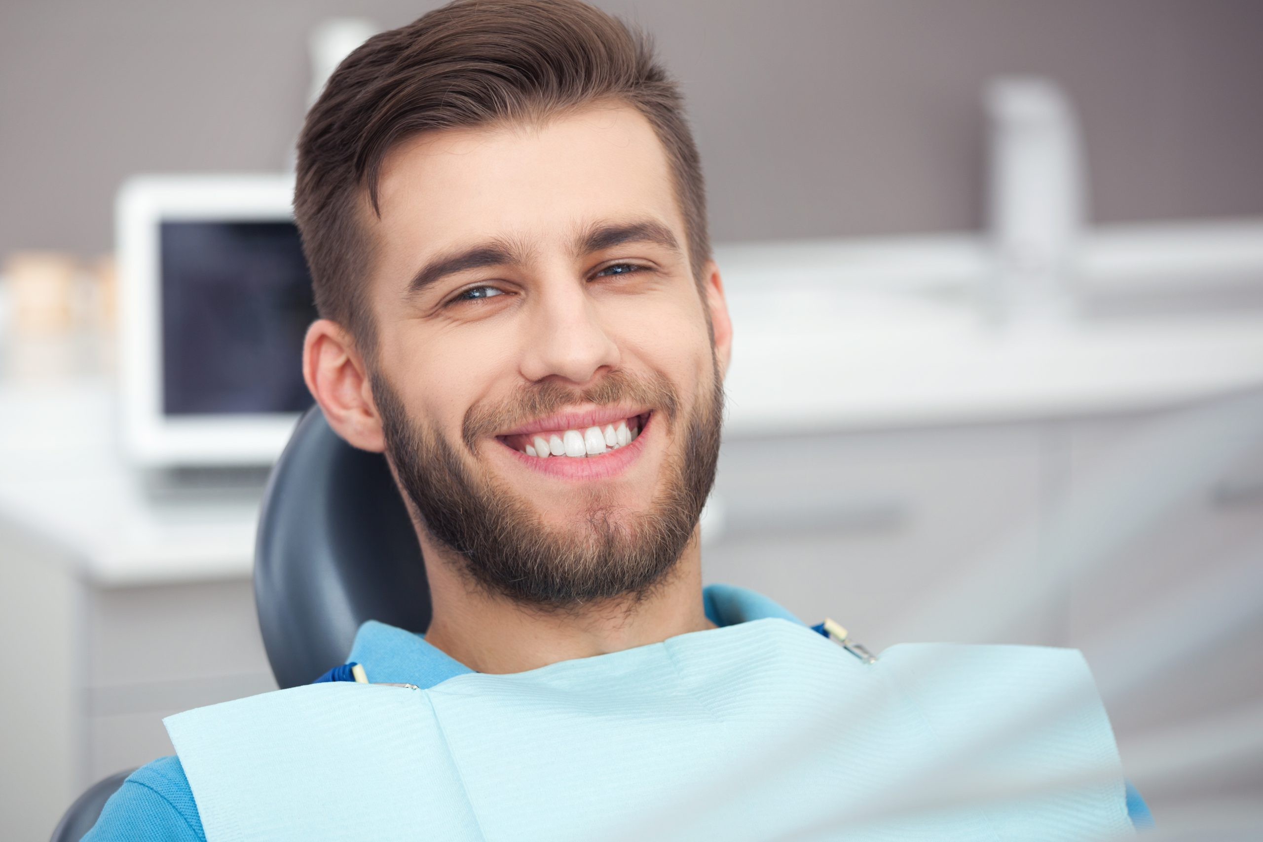 Portrait of happy patient in dental chair receiving the best orthodontic care in Surrey