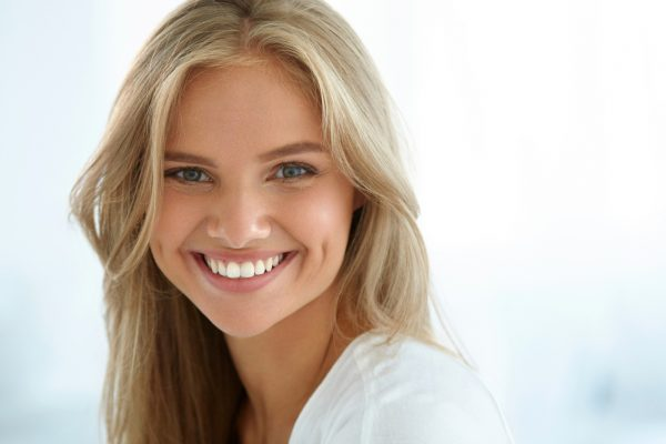 Happy patient receiving advanced tooth whitening treatment